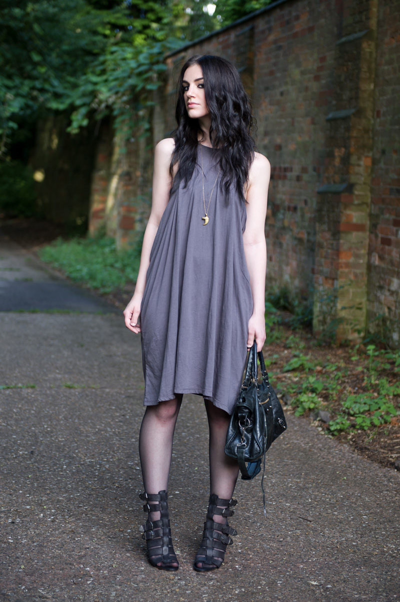 Fashion blogger Stephanie of FAIIINT wearing Cheap Monday taupe draped dress from Surfdome, Braza bandeau bra, Topshop black gladiator buckled wedges, Lion claw pendant, Balenciaga city bag. Casual dark style, street style.