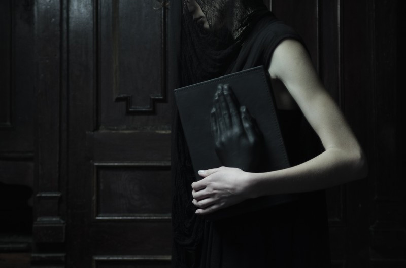 Konstantin Kofta 'Hug' collection book praying hands black leather clutch. Dark style, gothic, indepenent designer, lookbook
