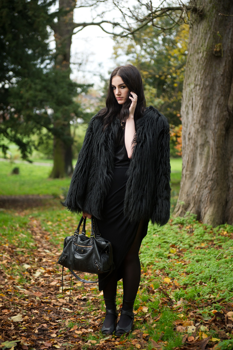 Fashion blogger Stephanie of FAIIINT wearing Lookbook Store faux fur black longhaired coat, H&M leather look tee, RockLove sacred geometry geo necklace, River Island asymmetric skirt, Rick Owens wedges, Balenciaga city bag. All black outfit, Game of Thrones crow coat
