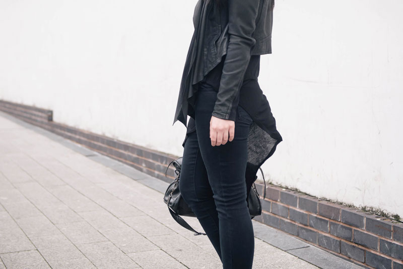 Fashion blogger Stephanie of FAIIINT wearing Barneys Originals draped leather jacket, Topshop skinny jeans & asymmetric top, Balenciaga city bag. Casual all black street style outfit.