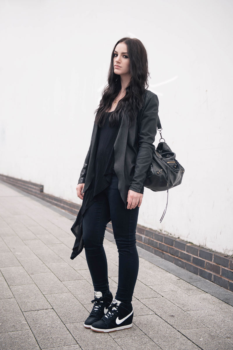Fashion blogger Stephanie of FAIIINT wearing Barneys Originals draped leather jacket, Topshop skinny jeans & asymmetric top, Nike Sky Hi High Dunk sneakers in black & white, Balenciaga city bag. Casual all black street style outfit.