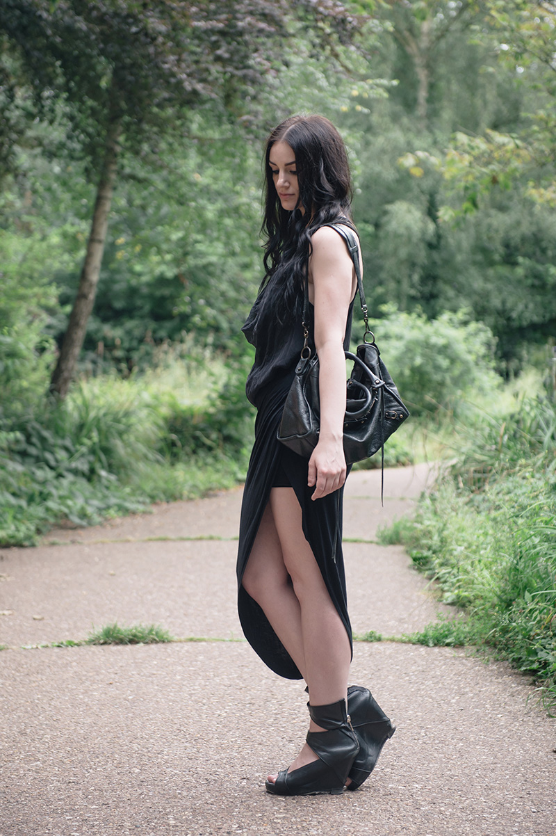 Fashion blogger Stephanie of FAIIINT wearing FOX via Log On Style draped silk tank top, River Island asymmetric skirt, YoungHearts designs gold dipped quartz necklace, Rick Owens wedges, Balenciaga city bag. All black goth summer street style outfit.