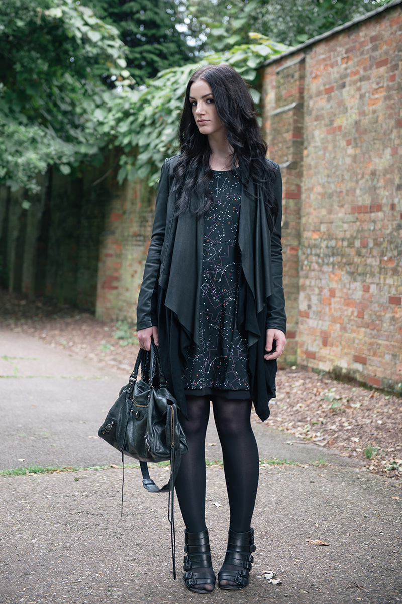 Fashion blogger Stephanie of FAIIINT wearing Barneys Originals draped leather jacket, ASOS cardigan, Yumi constellation print dress, Kurt Geiger buckle wedges, Balenciaga city bag. All black street style outfit.