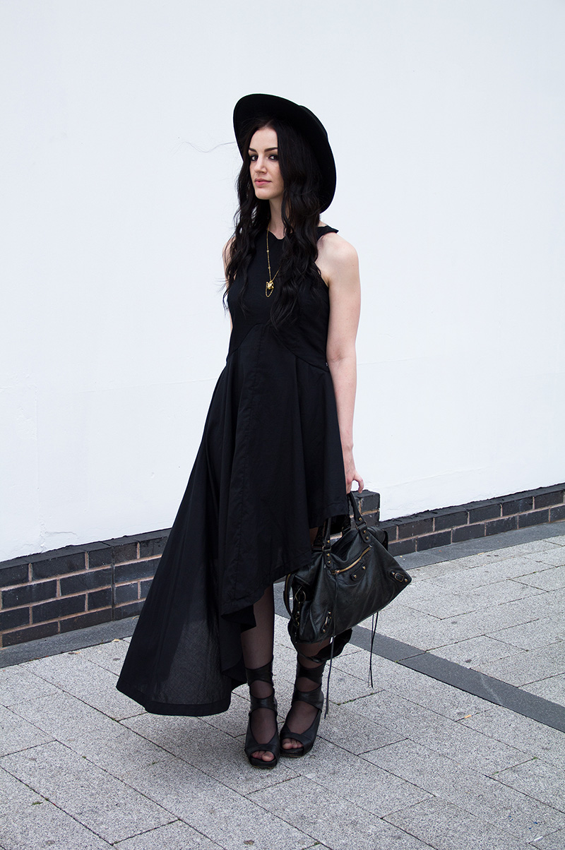 Fashion Blogger Stephanie of FAIIINT shot by Rosemary Pitts of Creatures Blog wearing FAIIINT asymmetric dress, Kasun London vampire heart necklace, Rick Owens wedges, Catarzi large fedora, Balenciaga city bag. All black, gothic street style outfit.