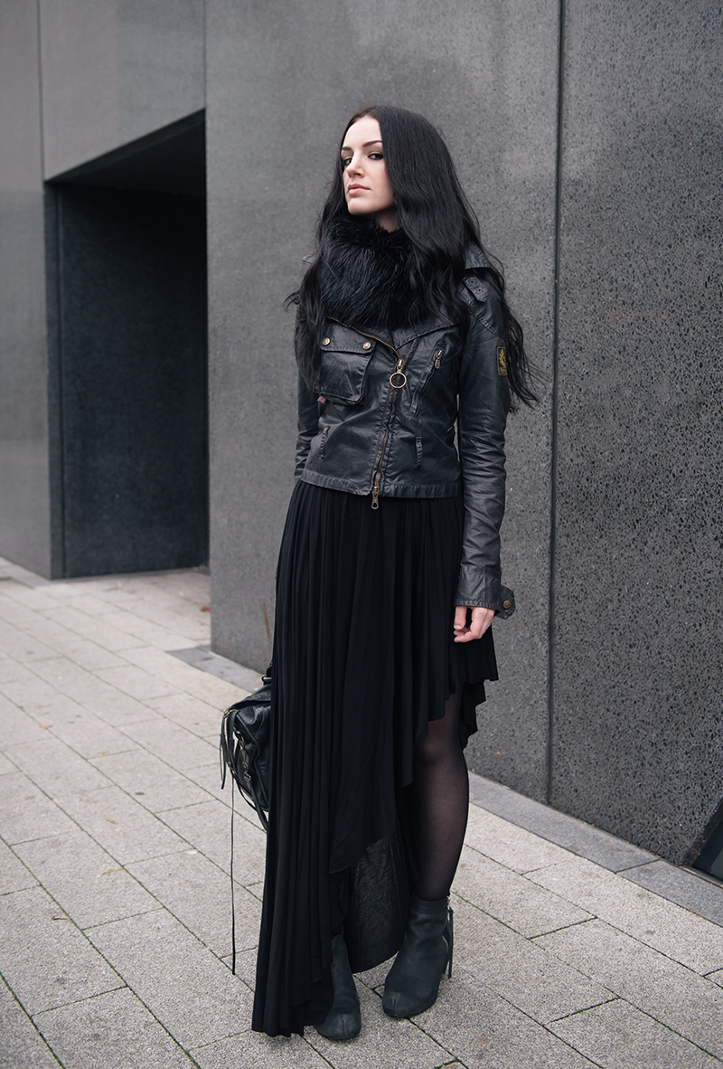 Fashion blogger Stephanie of FAIIINT wearing FAIIINT faux fur snood, Belstaff Sammy Miller waxed jacket, H&M asymmetric jersey maxi skirt, Kurt Geiger wedge boots, Balenciaga city bag. All black street style outfit.