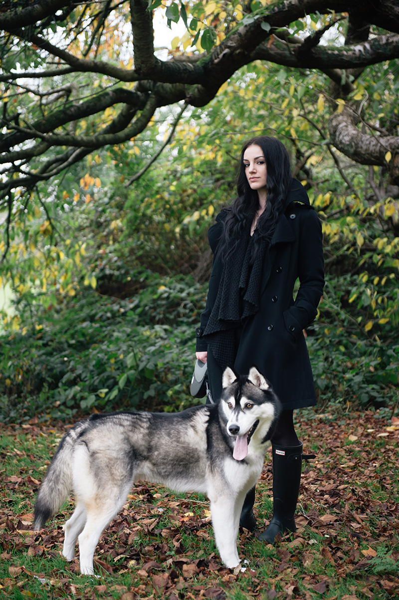 Stephanie Brown of FAIIINT wearing Topshop wool trench coat, ASOS draped chunky cardigan, Hunter wellies wellingtons, all black casual dog walk outfit with Nico siberian husky. Autumn in the park forest leaves on floor, beautiful nature.