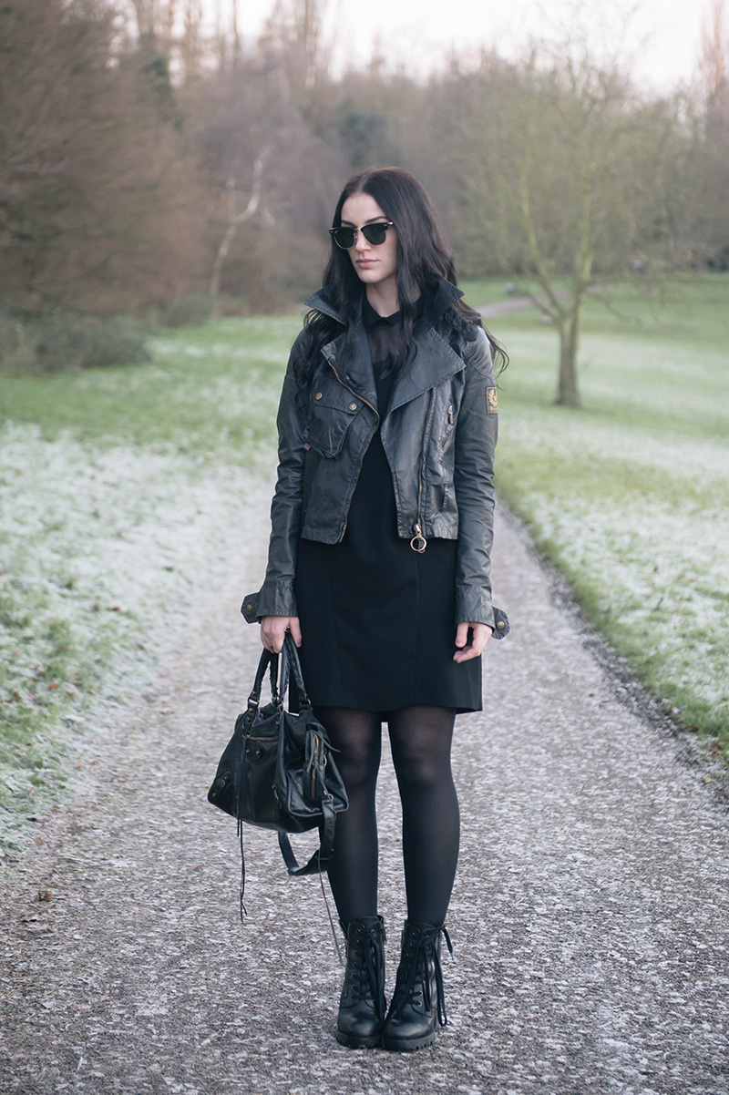 Fashion blogger Stephanie of FAIIINT wearing Ray Ban Clubmaster, Belstaff waxed sammy miller biker jacket, The Kooples shirt dress, Ash Poker Boots, Balenciaga City bag. All black casual outfit.
