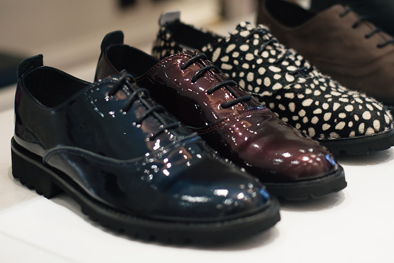 Fred's Shoes at PLFM London Shoe Show 2015. Classic brogues with heavy tread soles in metallic oxblood burgundy red & navy blue glossy patent leather and white & black spotted ponyhair.
