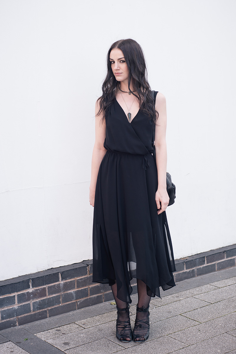 Fashion blogger Stephanie of FAIIINT wearing Warehouse chiffon wrap dress, Regal Rose Rua gemstone point choker, Regal Rose Cosmos Labradorite crystal pendulum necklace, Betty Jackson Black bag, Skin by Finsk lace up wedges. All black gothic witch street style summer outfit.