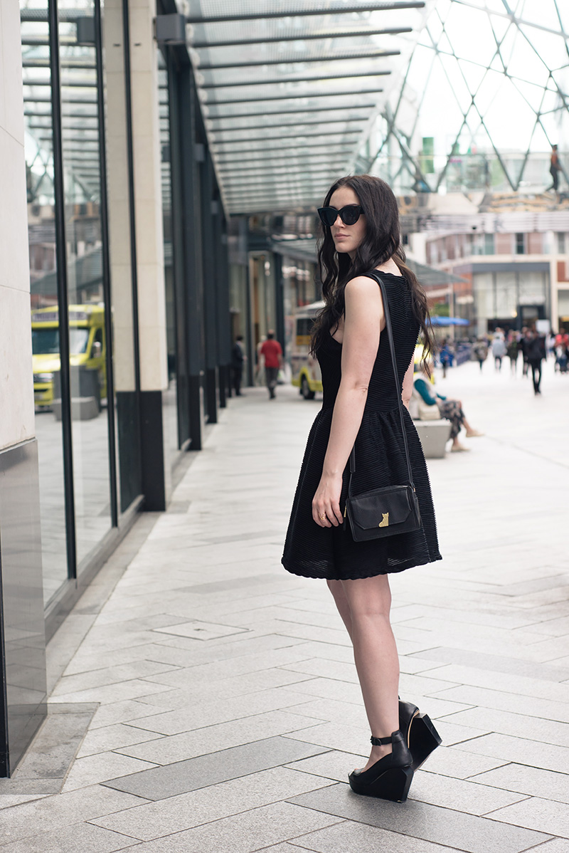 Fashion blogger Stephanie of FAIIINT wearing ASOS cateye sunglasses, Topshop textured skater dress, Nica Venice crossbody bag, Skin by Finsk wedges, Skin by Nair. Casual summer all black street style outfit.