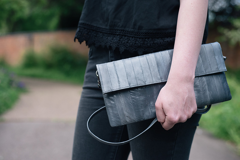 Fashion blogger Stephanie of FAIIINT wearing Makki elephant grey Nuevo Disco eel skin panel clutch bag.