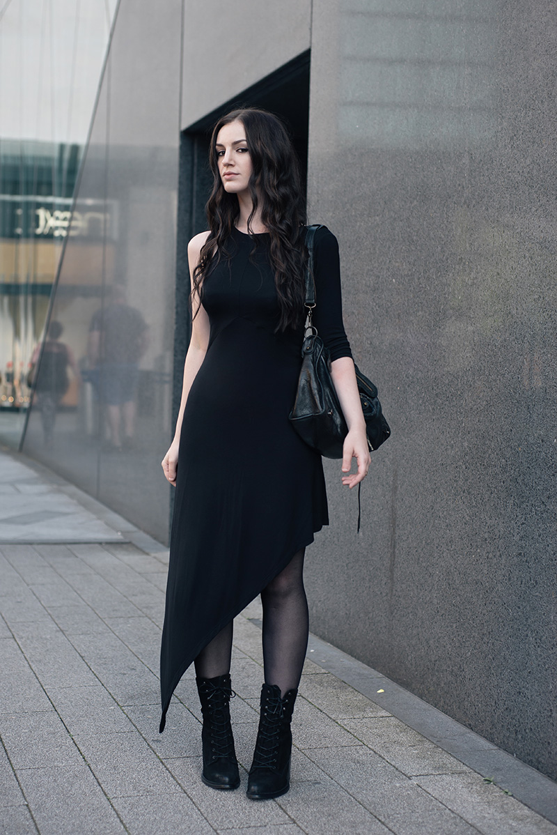 Fashion blogger Stephanie of FAIIINT wearing FAIIINT asymmetric slash one sleeve jersey dress, Kurt Geiger lace up Saturn suede boots, Balenciaga City bag, A Weathered Penny brass rings. All black everything street style summer goth outfit.