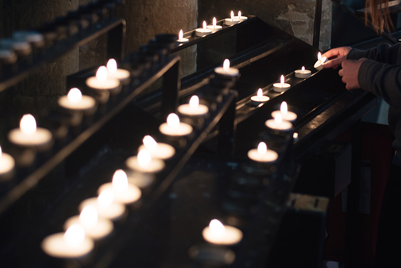 FAIIINT York weekend break. York Minster Cathedreal girl lighting a prayer candle.