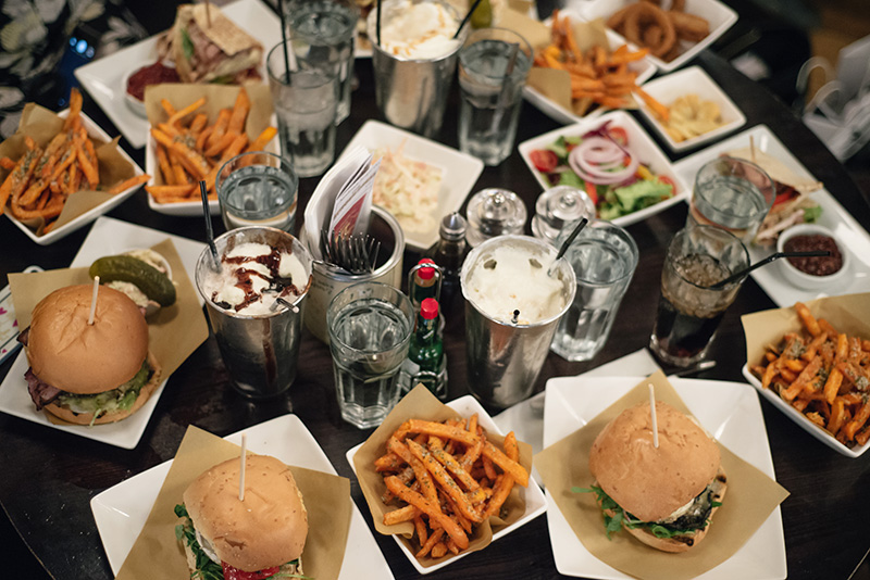 FAIIINT Handmade Burger Co at Highcross Leicester. View from above of table of burgers, sweet potato fries and shakes.