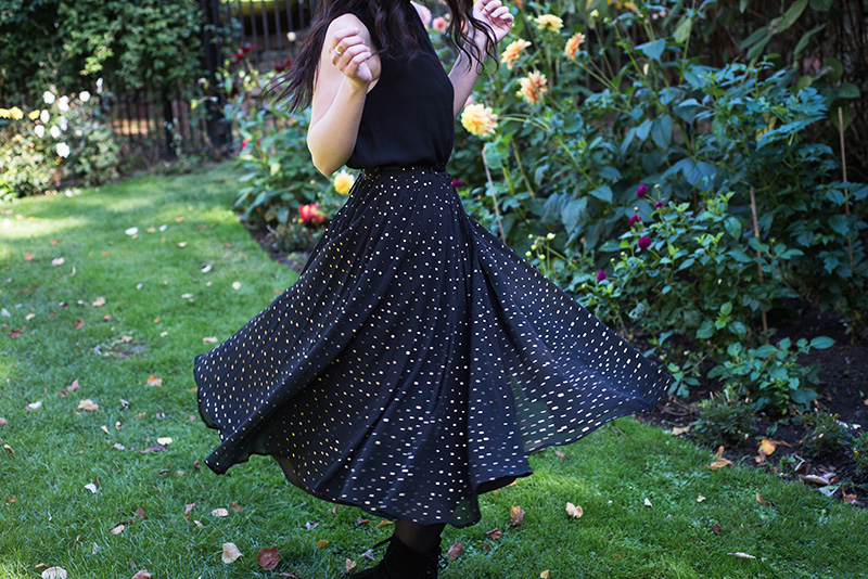 Fashion blogger Stephanie of FAIIINT wearing Yumi sleeveless blouse, Yumi gold spot polka dot pleated black chiffon midi skirt. Twirling around, outfit details.