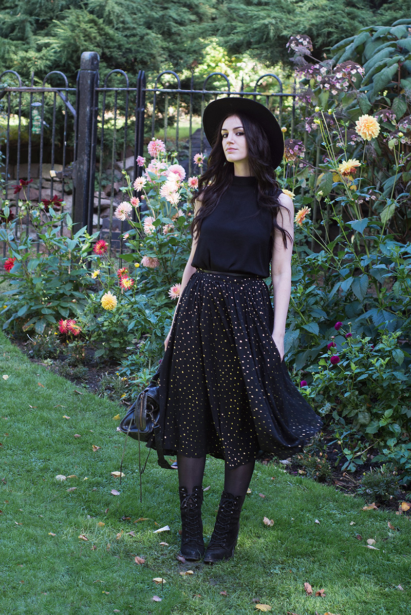 Fashion blogger Stephanie of FAIIINT wearing Catarzi fedora, Yumi button back sleeveless top, Yumi gold spot polka dot pleated chiffon midi skirt, Kurt Geiger 'Saturn' lace up boots and Balenciaga city bag. All black everything, dark street style outfit.