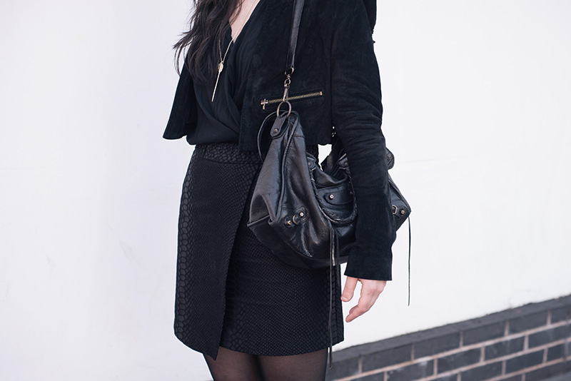 Fashion blogger Stephanie of FAIIINT wearing Topshop suede cropped jacket and snake texture wrap skirt, River Island Draped Blouse, Bloody Mary Metal Lovehunters Arrow Silver Necklace, Balenciaga City Bag. All black everything dark street style outfit.