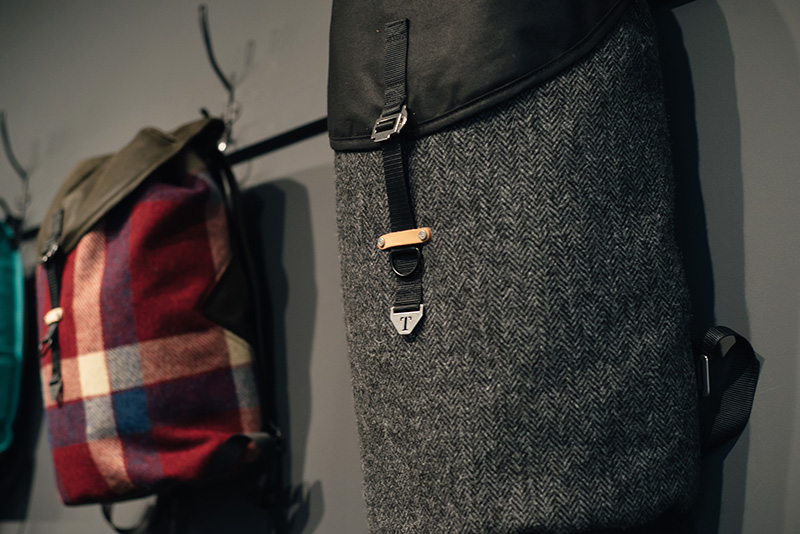 FAIIINT Trakke Glasgow studio. Krukke backpack bag in grey herringbone Harris Tweed and red check.