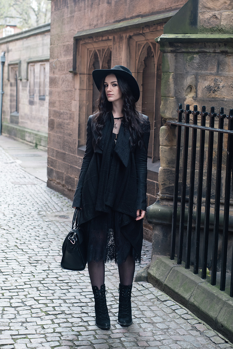Fashion blogger Stephanie of FAIIINT wearing Catarzi fedora, Todd Lynn x Topshop cropped jacket, H&M draped waterfall cardigan, SheIn lace dress, Kurt Geiger saturn lace up boots. All black everything dark street style outfit.