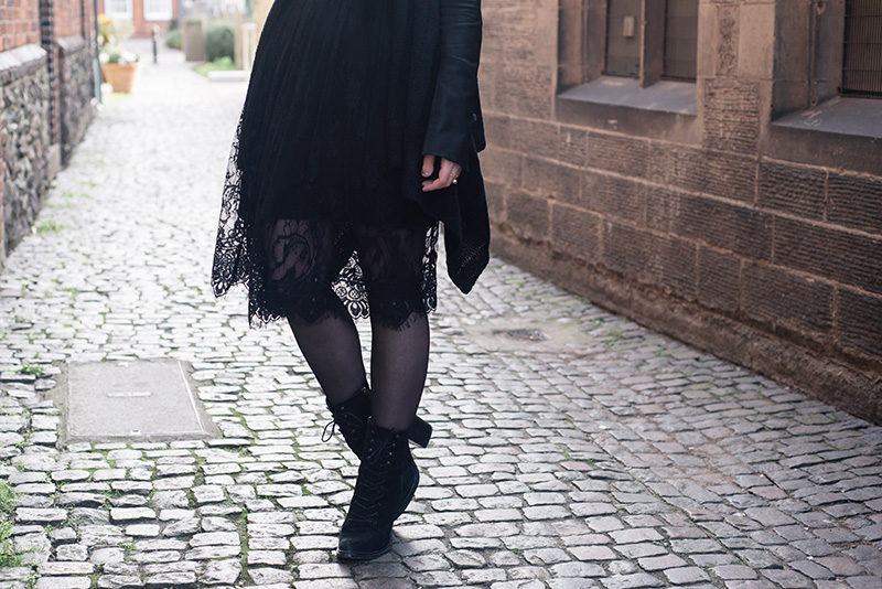 Fashion blogger Stephanie of FAIIINT wearing H&M draped waterfall cardigan, SheIn lace dress, Kurt Geiger saturn lace up boots. All black everything dark street style outfit.