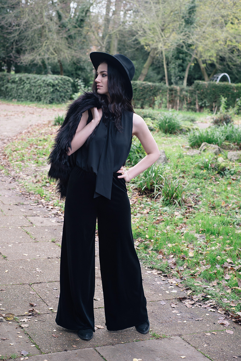 Fashion blogger Stephanie of FAIIINT wearing Catarzi fedora, H&M Faux fur jacket, F&F chiffon and velvet jumpsuit, Kurt Geiger boots, Betty Jackson Black bag. All black everything dark style 70s outfit.