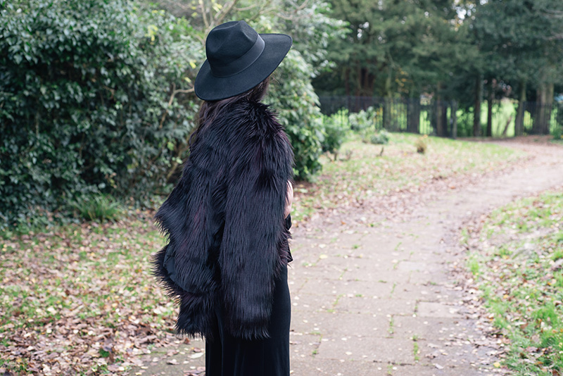 Fashion blogger Stephanie of FAIIINT wearing Catarzi fedora, H&M Faux fur jacket, F&F chiffon and velvet jumpsuit. All black everything dark style 70s outfit.