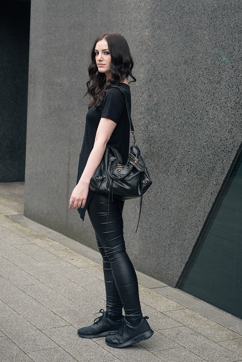 Fashion blogger Stephanie of FAIIINT wearing H&M asymmetric tee shirt, New Look coated jeans, Nike triple black Air Max Tavas trainers, Hvnter Gatherer Lacustrine necklace, Balenciaga city bag. All black everything casual goth dark street style outfit..