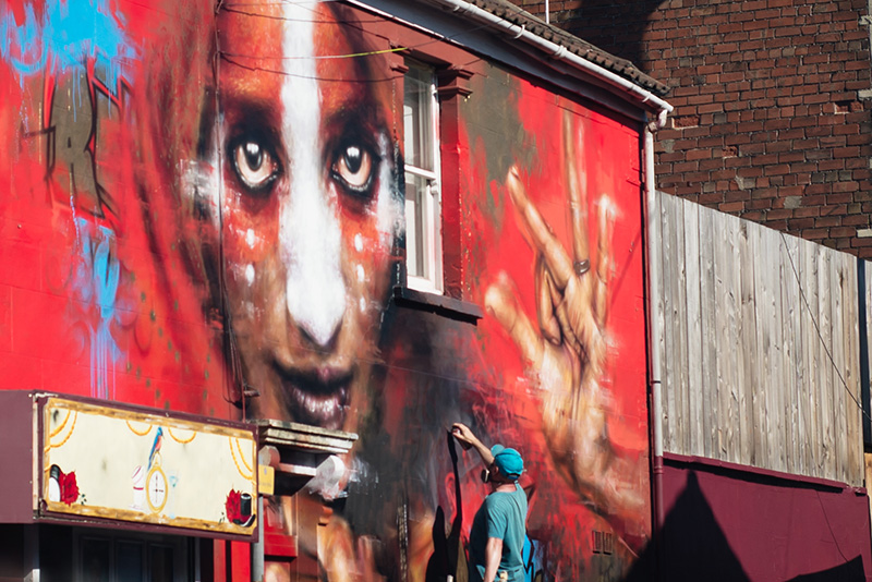Bristol Upfest street art festival. Artist painting large mural on building.