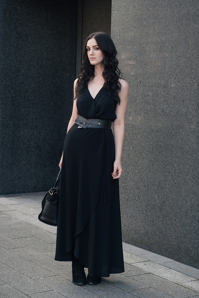 Fashion blogger Stephanie of FAIIINT wearing River Island draped top, New Look wrap maxi skirt, Pieces leather belt, Ailsigr jewellery, Kurt Geiger Saturn boots. All black everything summer street style outfit.