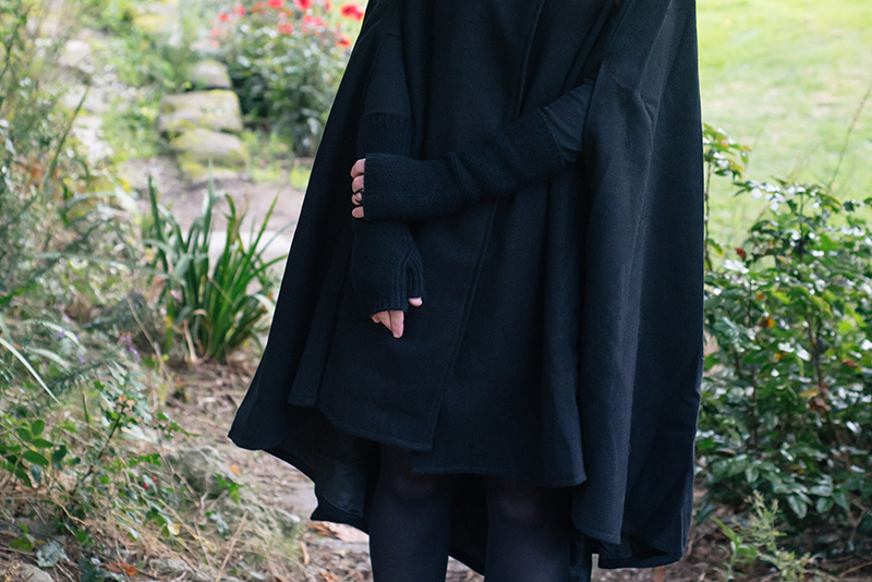 Fashion blogger Stephanie of FAIIINT wearing Necessary Evil Morrigan wool cape, Black.co.uk cashmere wrist warmers, The Rogue + The Wolf Occult ring. All black gothic autumn outfit details.