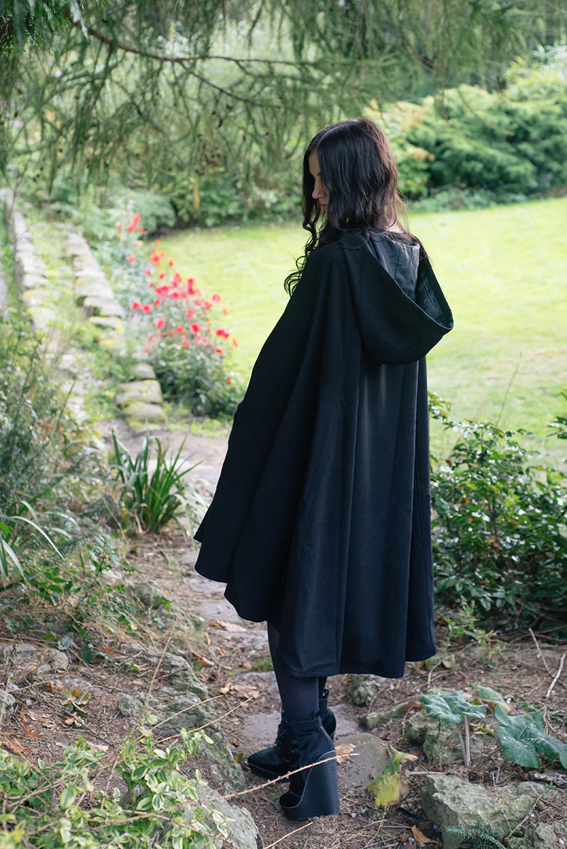 Fashion blogger Stephanie of FAIIINT wearing Necessary Evil Morrigan wool cape, Black.co.uk cashmere wrist warmers, The Rogue + The Wolf Occult ring, Kurt Geiger Solar ponyhair wedge lace up boots. All black gothic autumn outfit.