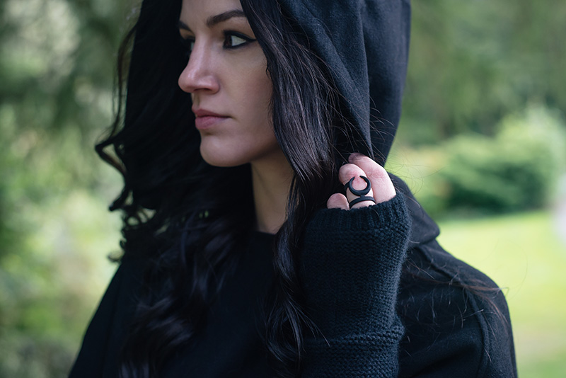 Fashion blogger Stephanie of FAIIINT wearing Necessary Evil Morrigan wool cape with hood, Black.co.uk cashmere wrist warmers, The Rogue + The Wolf Occult ring. All black gothic autumn outfit.