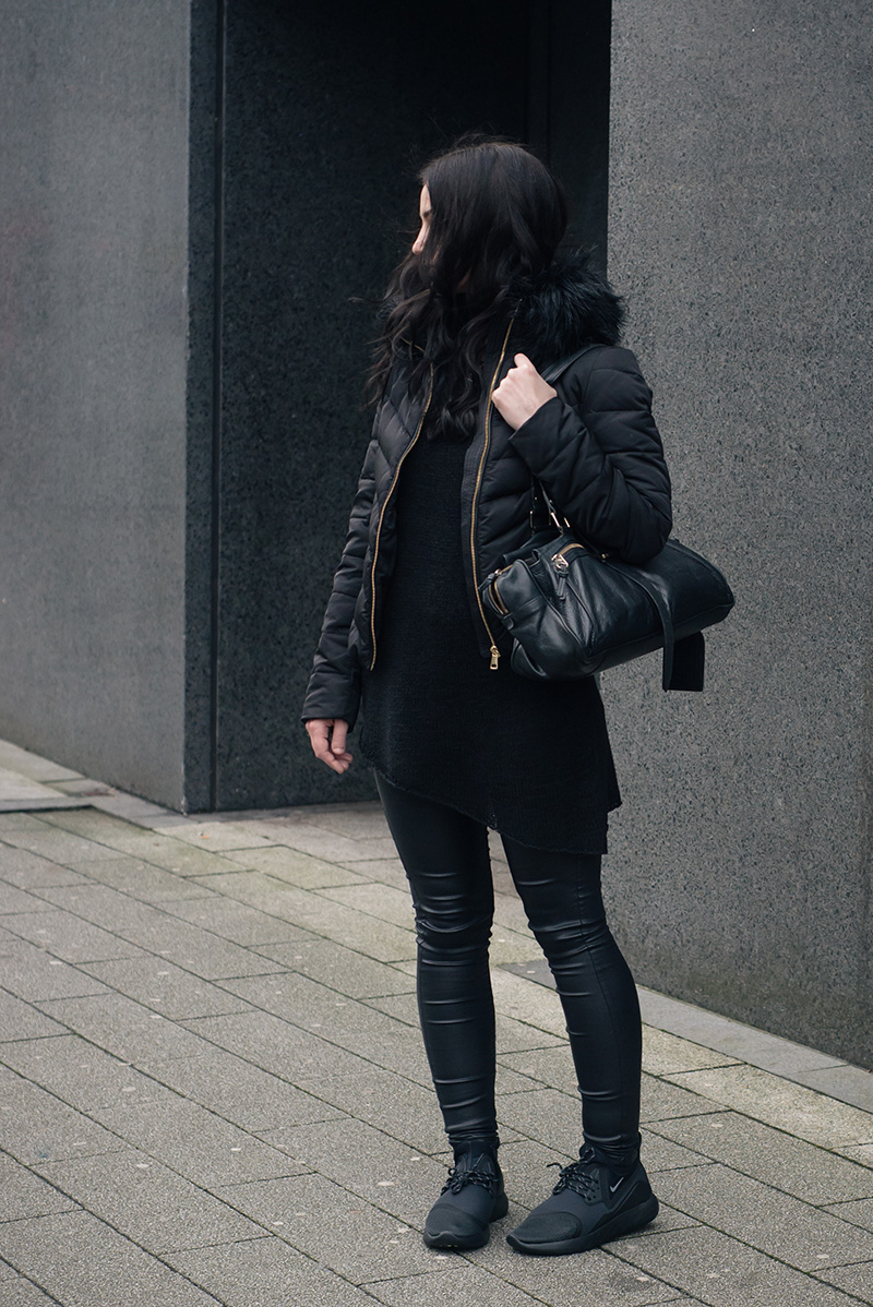 Fashion blogger Stephanie of FAIIINT wearing H&M quilted padded down jacket with faux fur collar, H&M asymmetric jumper, New Look coated skinny jeans, Nike black LunarCharge trainers, Mulberry Mabel bag. All black winter street style outfit.