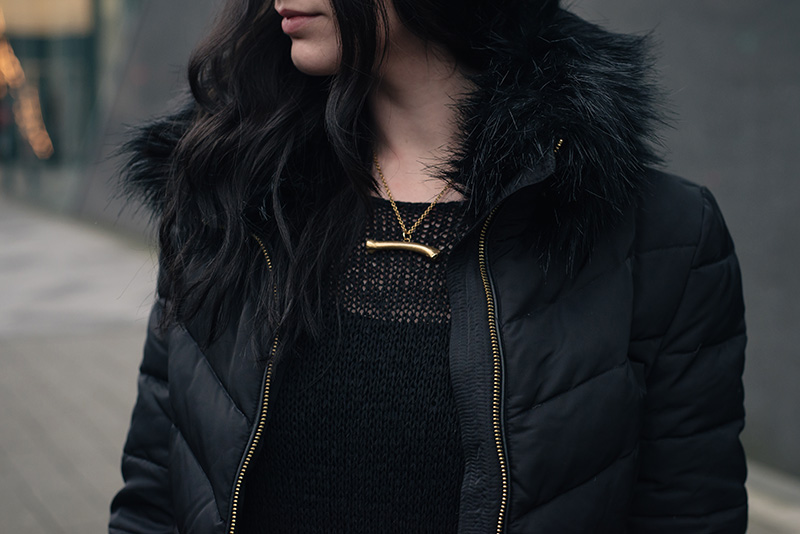 Fashion blogger Stephanie of FAIIINT wearing H&M quilted padded down jacket with faux fur collar, Sara Gunn gold bone necklace. All black outfit details.