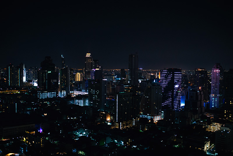 Bangkok Thailand city skyline with skyscrapers at night from the top of Zoom rooftop sky bar.