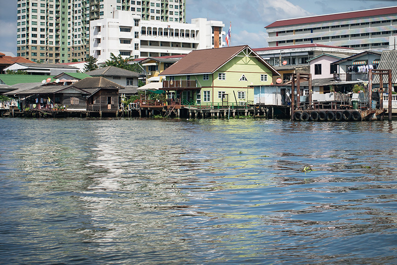 Bangkok Thailand Chao Phraya River ferry, brightly coloured wooden riverside homes on the water.