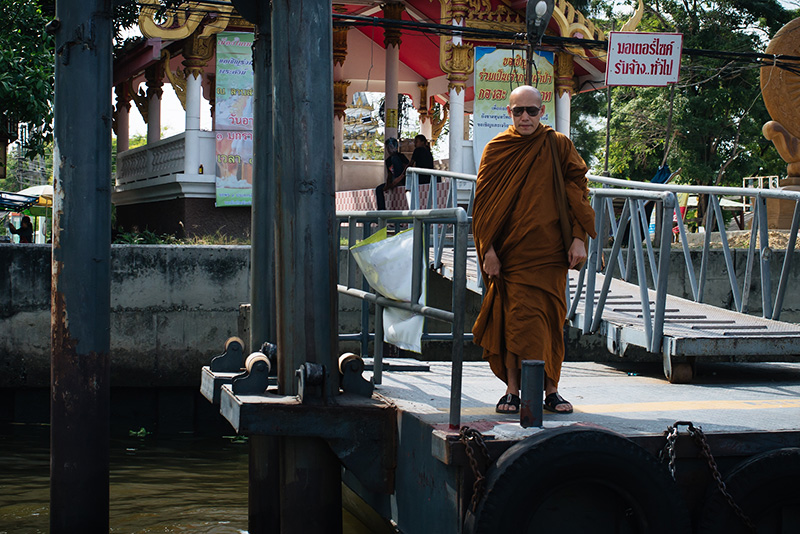 Bangkok Thailand Buddhist monk in sunglasses standing on the dock on the Chao Phraya River.