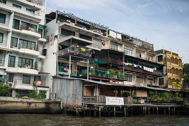 Bangkok Thailand Chao Phraya River riverfront apartments and balconies with colourful washing hanging up.