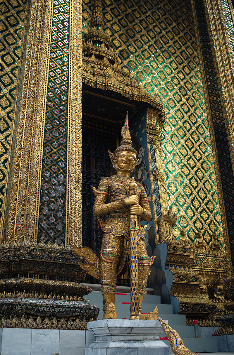 Temples of Bangkok Thailand, The Grand Palace and Wat Phra Kaew, glittering gold mosaic tiles and gold yaksha demon statue guardian at the entrance to Phra Mondop.