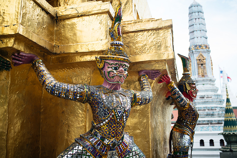 Temples of Bangkok Thailand, The Grand Palace and Wat Phra Kaew, colourful yaksha demon statues around gold stupa.