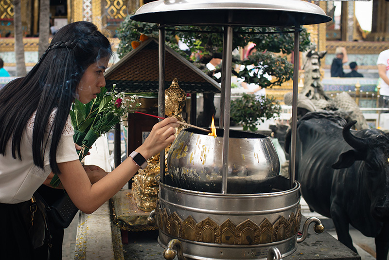 Temples of Bangkok Thailand, The Grand Palace and Wat Phra Kaew, girl lighting incence offering with flowers.