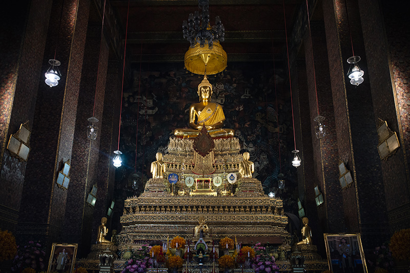 Temples of Bangkok Thailand, Wat Pho gold buddha statue with offerings inside central shrine.
