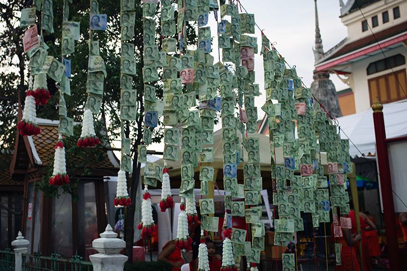 Temples of Bangkok Thailand, Wat Arun the Temple of Dawn, money offerings hanging across pathway.