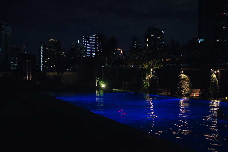 Anantara Sathorn Bangkok hotel Thailand pool area at night.
