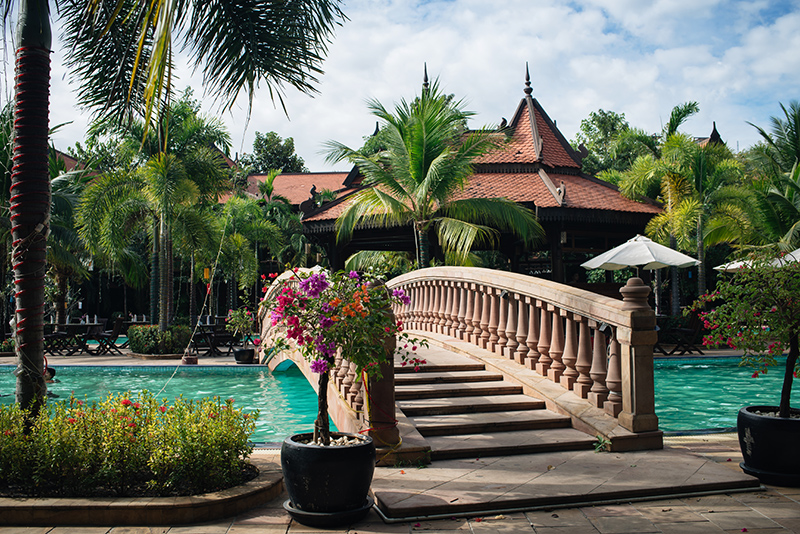 Sokhalay Angkor Villa Resort in Siem Reap Cambodia, tropical pool with flowers and bridge.
