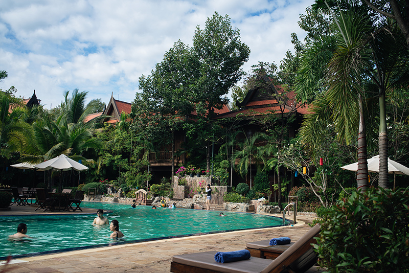 Sokhalay Angkor Villa Resort in Siem Reap Cambodia, pool area with palm trees and flowers.