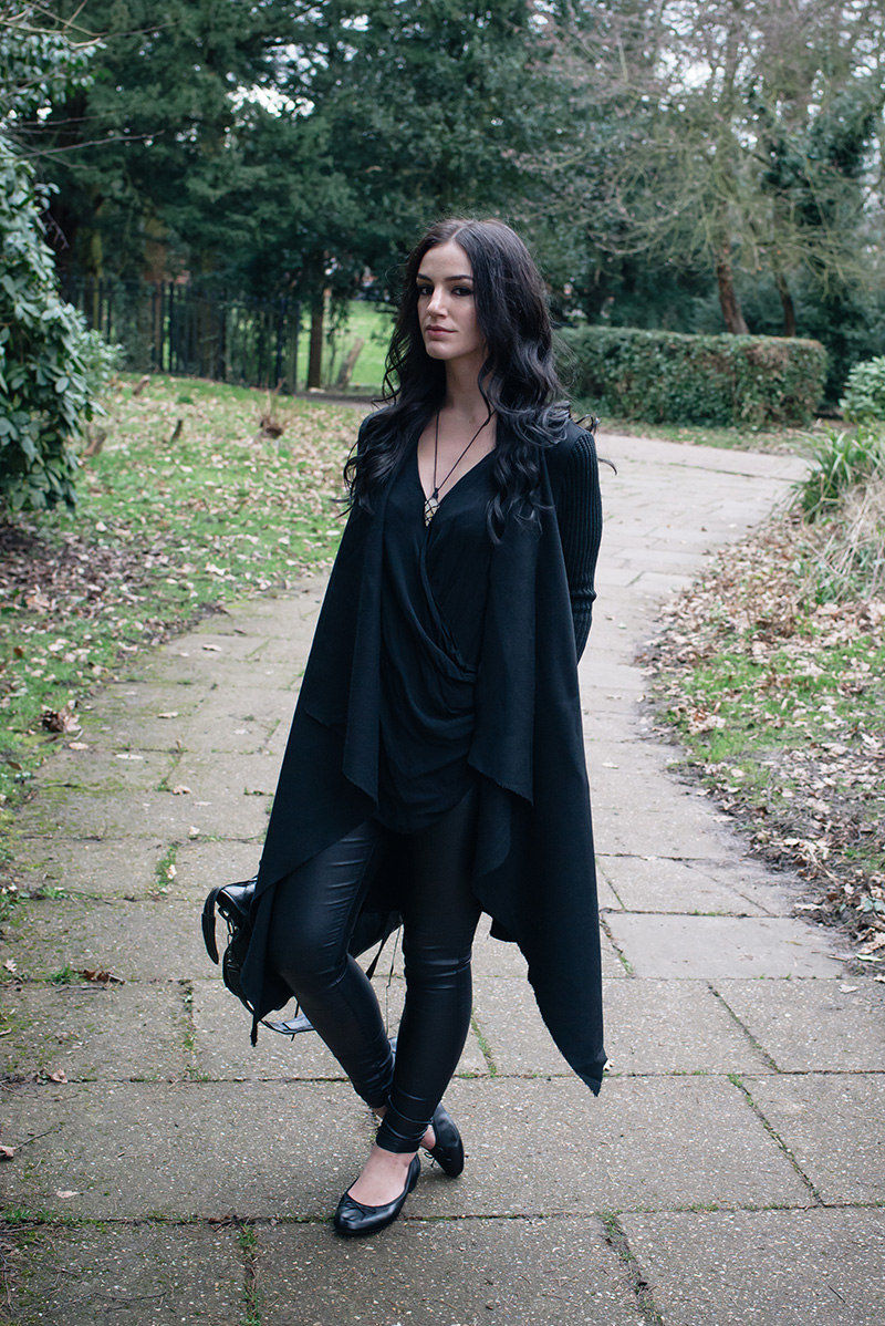 Fashion blogger Stephanie of FAIIINT wearing H&M Draped coat jacket, River Island draped top, New Look coated skinny jeans, Clarks ballet flats shoes, Sudio Sweden wireless headphones. All black everything goth dark street style outfit.