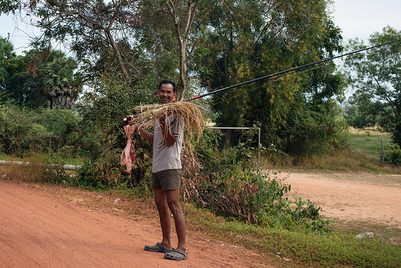 Motorbiking through the Siem Reap countryside in Cambodia. Local fisherman on the road.