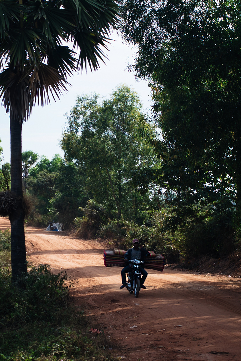 Motorbiking through the Siem Reap countryside in Cambodia, local on motorbike carrying rugs and blankets.