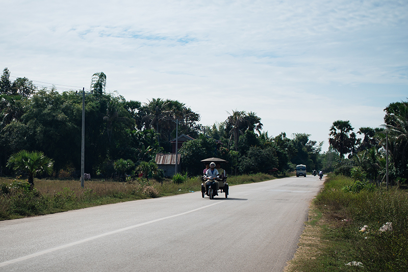 Motorbiking through the Siem Reap countryside in Cambodia, tuk tuks on the road.